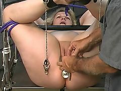 Thick lesbian girl has her asshole stuffed with metal butt plug after clamping